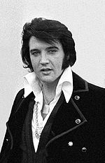 Posed photo of Elvis, shoulders and chest, wearing a shirt with a large, white collar and a coat with big lapels, medallions around his neck.