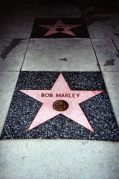 A five pointed pink star inlaid in the sidewalk with Bob Marley written on it.