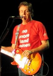 "McCartney, in his late sixties, playing an orange electric guitar and wearing a red shirt that bears, in white writing, the words ""no more land mines."" His eyes are closed."