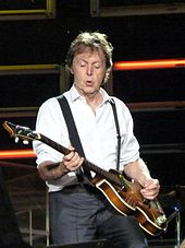 A man in his sixties, wearing a white shirt and black suspenders during a concert, playing a bass guitar.