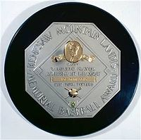 "A black circle with an octagonal silver plaque in the middle. The edge of the plaque reads ""KENESAW MOUNTAIN LANDIS AWARD BASEBALL MEMORIAL"". In the middle of the octagon is a baseball diamond which contains, from the top, a man's face in gold, ""Most Valuable Player"", the winner's league, his name in a gold rectangle, and his team."