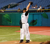 A man stretches his arms behind his head while wearing a baseball glove and a white baseball uniform with green sleeves and cap.