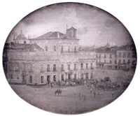 Photograph showing the Imperial Palace in Rio de Janeiro with carriages and mounted honor guard in the square fronting the palace.