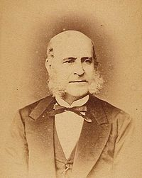 A photograph showing the head and shoulders of an older, balding man with long sideburns dressed in a dark suit, vest and bow tie