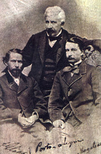 An old photograph depicting two dark-haired men seated in the foreground and a white-haired man standing behind