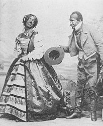 Two blackface performers on stage, one a man dressed in fancy woman's clothes, the other in dress attire, bowing with his hat in his hand.
