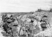 Heavy laden soldiers move through a communication trench during the daytime