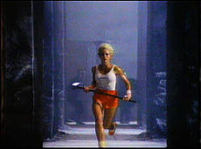 A young woman carrying a sledge hammer and wearing a white tank top with a drawing of a Macintosh runs from black figures in the background.