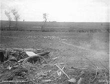Two soldiers operate a field gun from a dug-in position in an open field and reinforced with sandbags. Entrenching tools, spoil and broken vegetation lie around the emplacement, while a number of defoiliated trees stand in the middle distance.