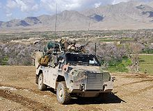 A camouflaged military vehicle on top of a hill. The valley behind the vehicle contains several complexes of buildings and flowering trees. A steep mountain range is in the background
