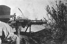 A soldier lies amongst the grass in the prone position behind a machine gun which he is holding in the shoulder