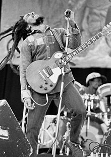Black and white picture of a man with long dreadlocks playing the guitar on stage.