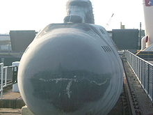 Frontal view of a small submarine in a dockyard.