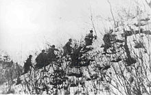 A group of soldiers climbing up a snow covered hill