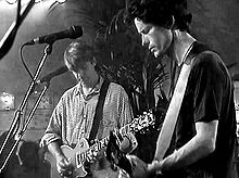 Two men holding guitars onstage. Man at left is looking downwards, right hand strummings strings, left hand on fret board. Second man is half turned with his left hand high on the fret board.