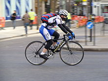 A man with sports clothes and a white helmet on a bicycle on a road.