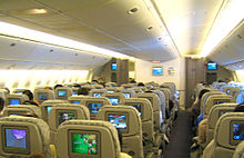 Airline economy cabin. Rows of seats arranged between two aisles. Each seatback has a monitor.