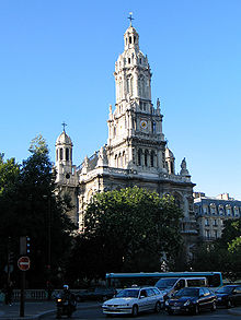 A 19th-century church in the French style, in light coloured stone, with a central tower with rounded top and smaller towers set back to left and right. The sky is blue. There are trees in leaf, and some cars parked in front of the church.