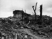 Heavily laden soldiers trudge through mud past the shattered remains of a concrete structure. Around them broken trees, steel beams and other pieces of debris have been strewn