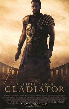 A man standing at the center of the image is wearing armor and is holding a sword in his right hand. In the background is the top of the Colosseum with a barely visible crowd standing in it. The poster includes the film's title, cast credits, and release date.