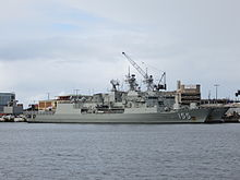 Colour photo of two grey-painted warships moored alongside a wharf. A large crane and several buildings are visible behind the ships.