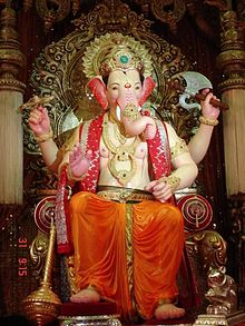 A sitting elephant-headed four-armed man statue, wearing gold ornaments, flower garlands and a orange dhoti.