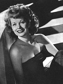Glamorous publicity shot of Lucille Ball from the waist up, dressed in a blue strapless gown and smiling.
