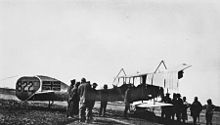 A group of men gather around a biplane. The Union Jack has been painted on to the tail of the aircraft