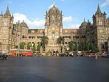 A brown building with clock towers, domes and pyramidal tops. Also a busiest railway station in India.[203] A wide street in front of it