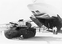 A cargo plane with its access door open, men, and a tank