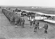 Men standing in files behind biplanes. They are wearing slouch hates, service jackets and breeches