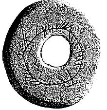 A grainy black-and-white image of a stone disc with a hole in its centre. The surface of the disk has a circle carved into it, which along with the central hole creates a concentric effect. Crude notches, mostly short straight lines, but with some zig-zags, have been carved along and near the circumference of the circle.
