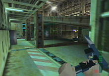 A metallic room with colums and computers located in the farthest side. A hand holding and reloading a gun is seen on the bottom right corner. A crosshair and graphics symbols representing ammunition are also visible.