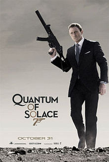 "A man in a business suit holding a machine gun stands on a desert. To his left is the title ""Quantum Of Solace"" in black letters – except the 'O's, which are golden and make a diagonal straight line with a 7 resembling a gun."