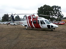 A helicopter painted red and white at rest on grass. Cars are parked in the background.