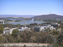 A group of multi-story office buildings. A lake, mountains and a jet of water are visible in the background.