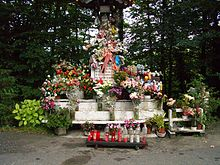 A statue, covered with flowers.