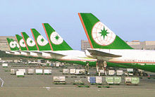 Row of eight aircraft tails in identical livery, lined at airport terminal, surrounded by cargo and equipment.