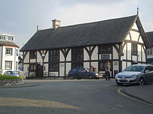A half timbered building of two floors, with four sets of leaded windows to the front aspect and one set to the side. The build has a steep, slate roof, with a single chimney placed left of centre. Steps and a ramp lead up to its single visible entrance.