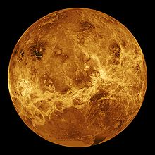 A false color image of Venus. Ribbons of lighter color stretch haphazardly across the surface. Plainer areas of more even colouration lie between.