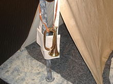 Bugle on leather strap hangs outside a small tent.