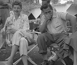 Casual shot of Ball and Arnaz outside, sitting in director chairs. Ball is smiling slightly; Arnaz is looking the other way with his hand over his mouth.
