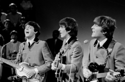 A black-and-white image of three men playing guitar. They are wearing grey buttoned-up suit jackets with ties underneath. An audience is visible behind them on the left.