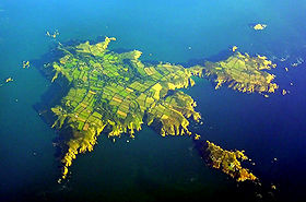 Aerial view of Sark; North is to the left of centre, Little Sark in the upper right and Brecqhou at bottom right.