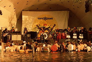 A crowd of people standing in water and listening to a band perform on stage.