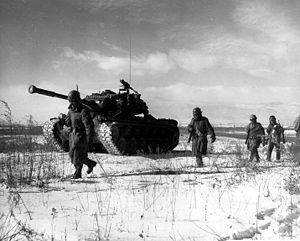 Men advancing through the snow with a Tank